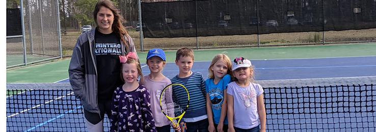instructor with kids learning tennis
